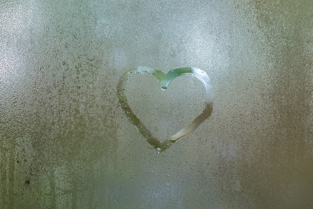 Forma de coração desenhada em uma janela molhada em um dia chuvoso Foto Premium
