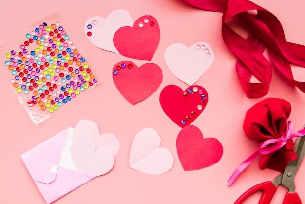 Forma de coração vermelho com fitas no fundo rosa Foto gratuita