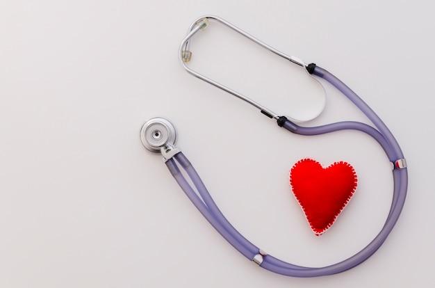 Forma de coração vermelho de têxteis com estetoscópio isolado no pano de fundo branco Foto gratuita