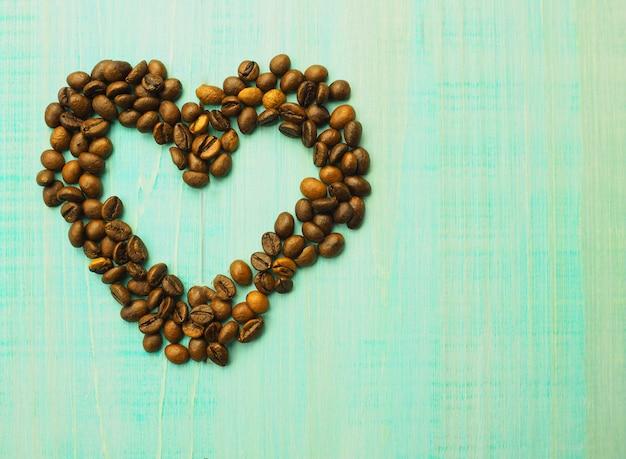 Forma do coração feita dos feijões de café na superfície de madeira. Foto Premium