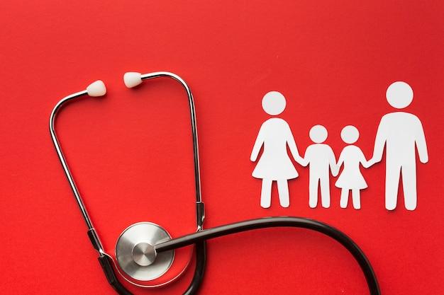 Formas de família de papelão com estetoscópio sobre fundo vermelho Foto gratuita