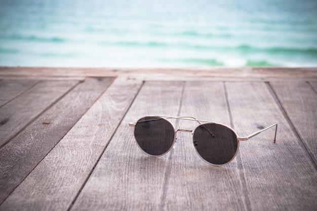 Forme óculos de sol no fundo azul do mar da tabela de madeira do vintage. férias de verão realmente relaxantes. Foto Premium