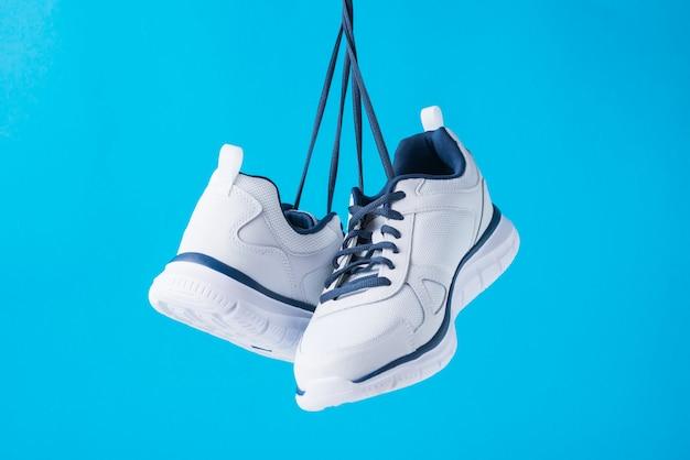 Forme sapatas masculinas do esporte em um fundo azul. tênis de homem estiloso para fitness, close-up Foto Premium