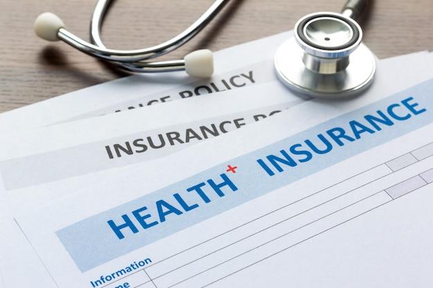 Formulário de seguro de saúde com estetoscópio na vista superior Foto Premium