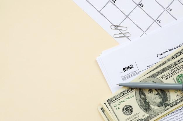 Formulário irs 8962 em branco ptc de imposto premium, em branco, com caneta e muitas notas de cem dólares na página do calendário Foto Premium