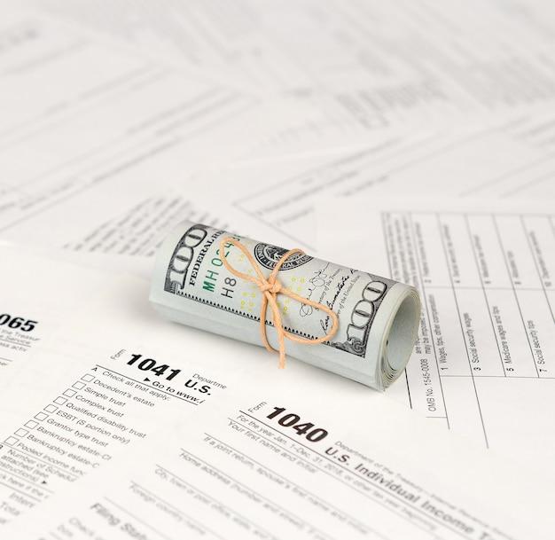 Formulários de imposto encontra-se perto de rolo de notas de cem dólares. restituição do imposto de renda Foto Premium