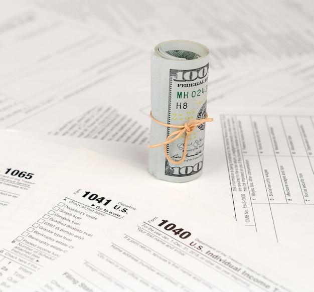 Formulários de impostos estão perto do rolo de notas de cem dólares. restituição do imposto de renda Foto Premium