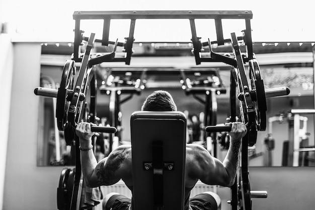 Forte fisiculturista treinando na academia Foto Premium