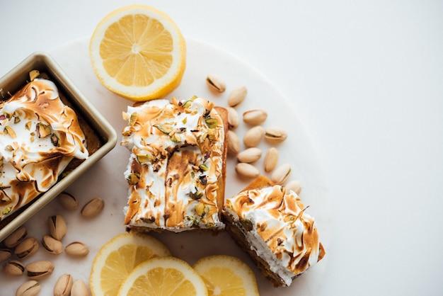 Foto aérea ampla de sobremesa saborosa bolo com nozes e limões em um prato branco e fundo branco Foto gratuita