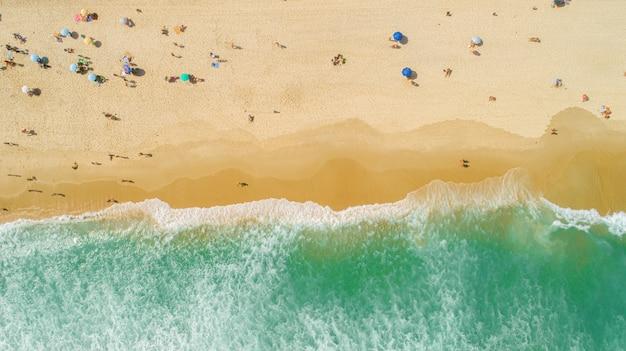 Foto aérea bloqueada de ondas quebrando na praia. guarda-chuvas de praia coloridos e pessoas aproveitando o verão. Foto Premium