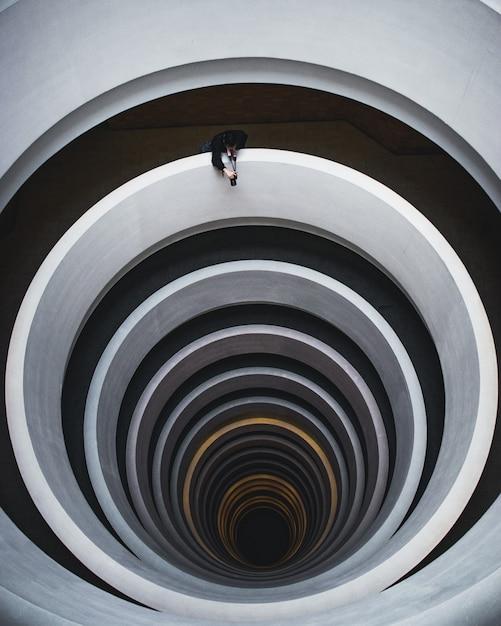 Foto aérea bonita de uma escada em espiral com um fotógrafo tirando uma foto da abertura Foto gratuita