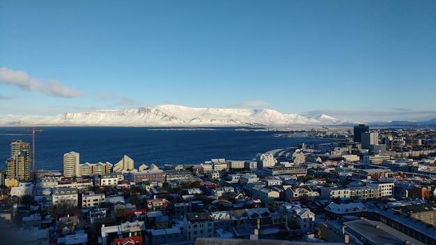 Foto aérea da cidade costeira de reykjavik com montanhas cobertas de neve em um céu azul Foto gratuita