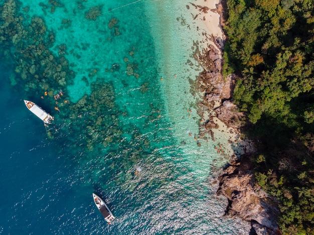 Foto aérea de barcos navegando na água perto da costa, coberta de árvores durante o dia Foto gratuita