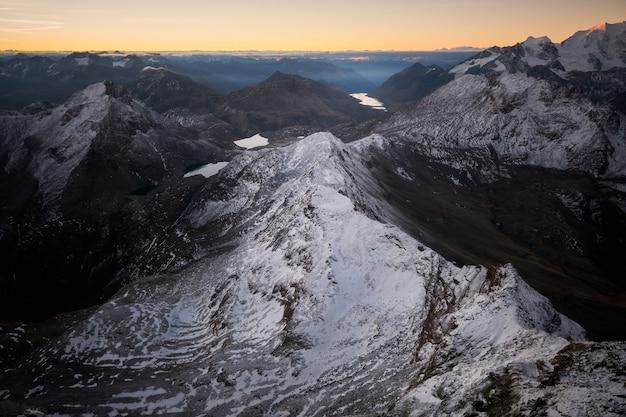 Foto aérea de montanhas nevadas com um céu claro Foto gratuita
