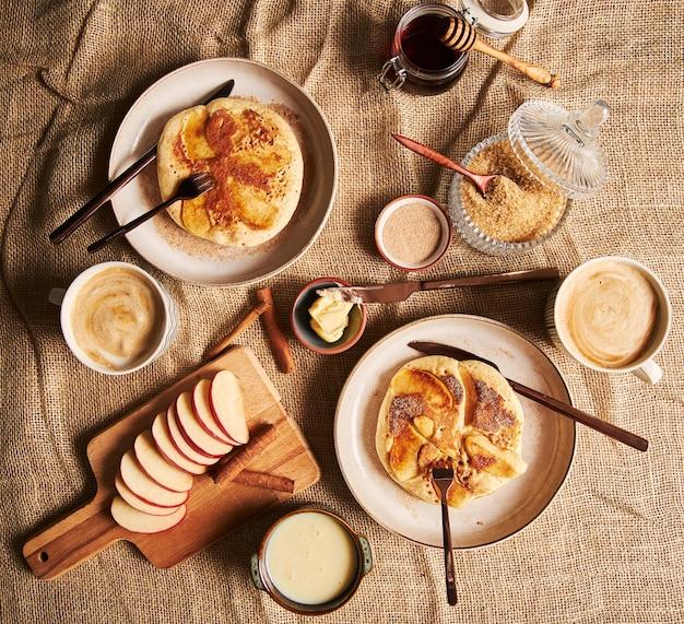 Foto aérea de panquecas de maçã, café, maçãs, mel e outros ingredientes de cozinha ao lado Foto gratuita