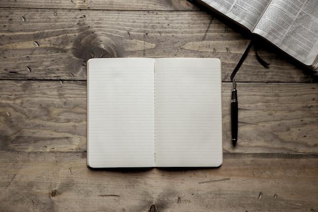 Foto aérea de um caderno em branco perto de uma caneta-tinteiro em uma superfície de madeira Foto gratuita