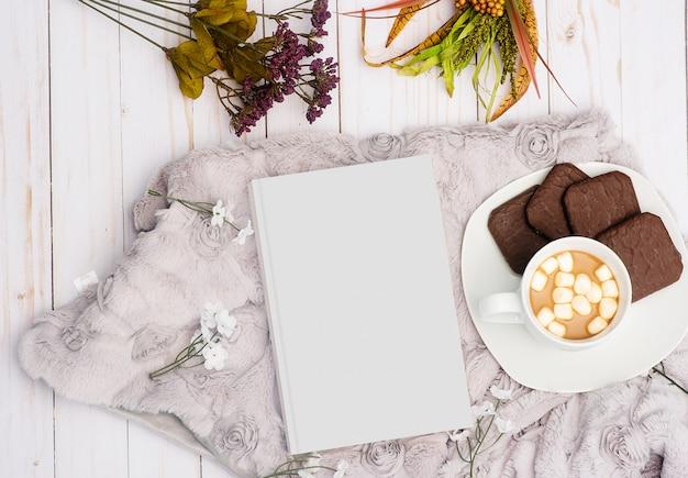 Foto aérea de um livro branco ao lado de uma bebida doce com biscoitos de chocolate num prato Foto gratuita