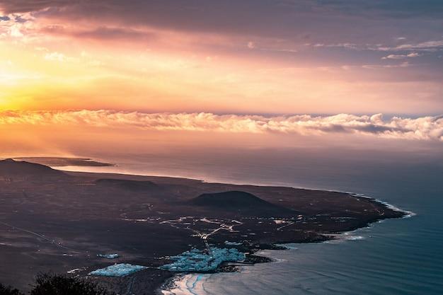 Foto aérea de uma bela cidade costeira à beira-mar com incríveis nuvens e luz do sol à esquerda Foto gratuita