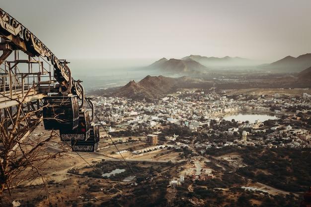 Foto aérea de uma cidade em um vale com um lago e montanhas rochosas e um teleférico abandonado enferrujado Foto gratuita