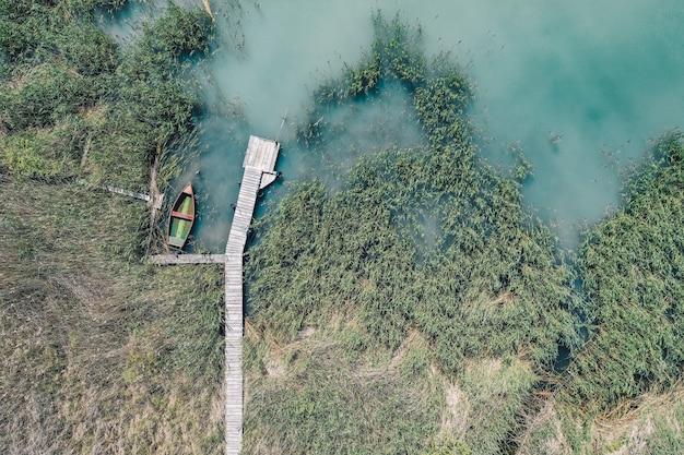Foto aérea de uma doca de madeira na costa com um barco de pesca ao lado Foto gratuita