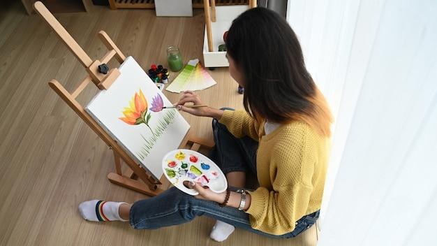 Foto aérea de uma jovem artista feminina está pintando na tela enquanto está sentada no chão de seu estúdio. Foto Premium