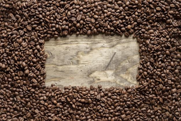 Foto aérea de uma moldura de grãos de café sobre uma superfície de madeira, excelente para o plano de fundo ou para escrever texto Foto gratuita