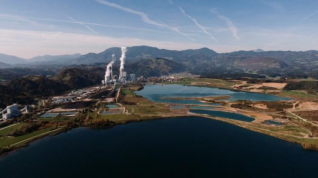 Foto aérea de uma paisagem cercada por montanhas e lagos com desastre industrial Foto gratuita