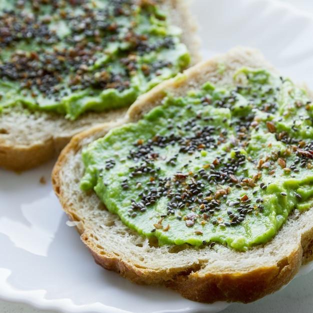 Foto aérea de uma pasta de pão com creme de abacate com sementes de chia Foto gratuita