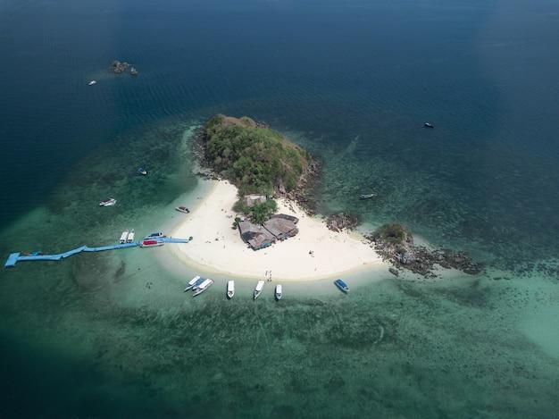 Foto aérea de uma pequena ilha com alguns prédios e barcos e um cais azul Foto gratuita