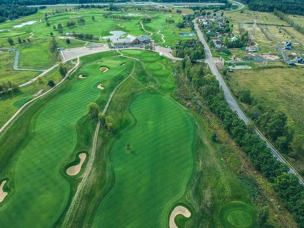 Foto aérea do clube de golfe, gramados verdes, árvores, estrada, cortadores de grama, Foto Premium