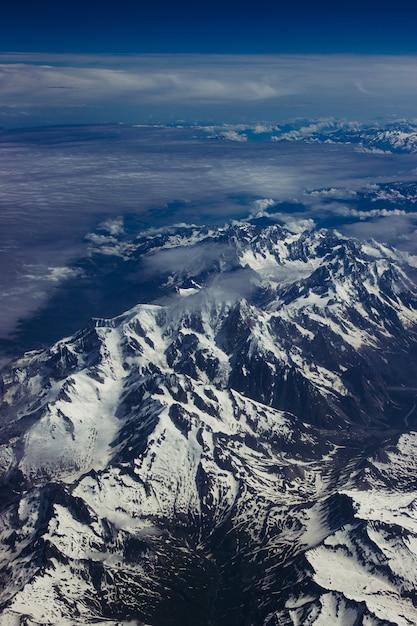 Foto aérea vertical do cenário montanhoso nevado sob o céu azul de tirar o fôlego Foto gratuita
