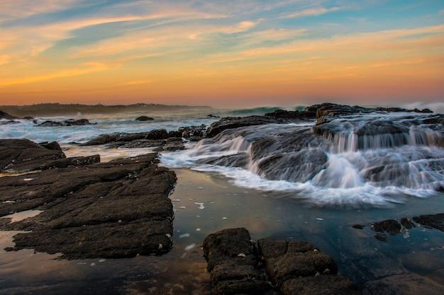Foto ampla da praia com formações rochosas durante o pôr do sol com um lindo céu Foto gratuita