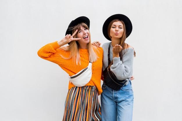 Foto ao ar livre de duas amigas alegres, passando grande tempo juntos posando em branco Foto gratuita