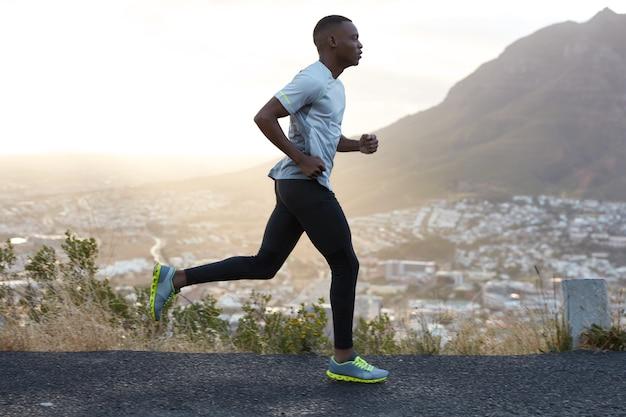 Foto ao ar livre de homem ativo de pele escura correndo pela manhã, tem treinos regulares, vestido com agasalho e tênis confortáveis, concentrado na distância, vê o final à distância. Foto gratuita