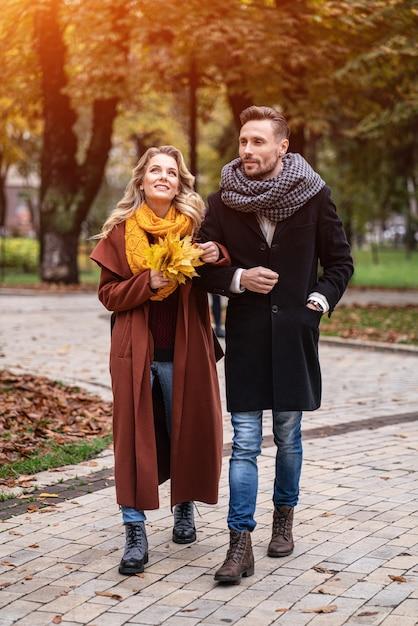 Foto ao ar livre de um jovem casal apaixonado caminhando por um caminho em um parque de outono Foto Premium