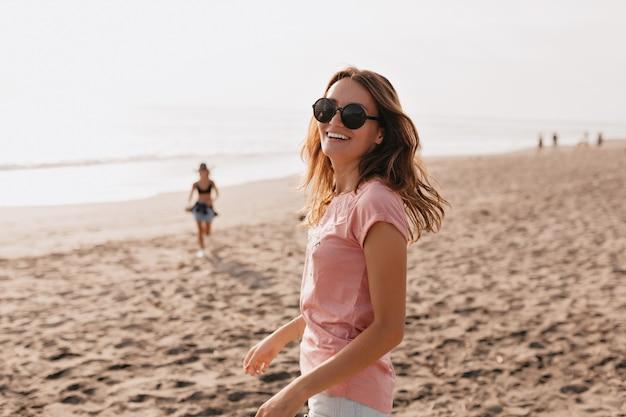 Foto ao ar livre de uma jovem modelo feminina feliz com uma camiseta de verão em pé contra o céu azul e a areia da praia mulher se divertindo em um dia de verão Foto gratuita