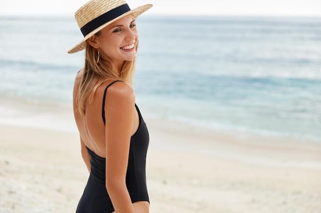 Foto ao ar livre de uma mulher satisfeita com a pele queimada pelo sol, usa chapéu de palha e maiô, caminha pela costa, desfruta de bom descanso à beira-mar, olha feliz para os amigos. pessoas e férias de verão Foto gratuita