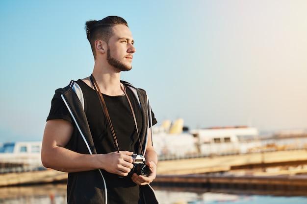 Foto ao ar livre do jovem fotógrafo masculino bonito em pé no porto, olhando como o pôr do sol se reflete no mar e nas ondas, sonhando ou inventando a idéia de tirar foto de belas paisagens com a câmera Foto gratuita