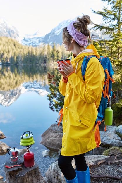 Foto ao ar livre vertical de hicker feminina pensativa segurando uma bebida quente em uma xícara de chá, fazendo a bebida em equipamento turístico especial Foto gratuita