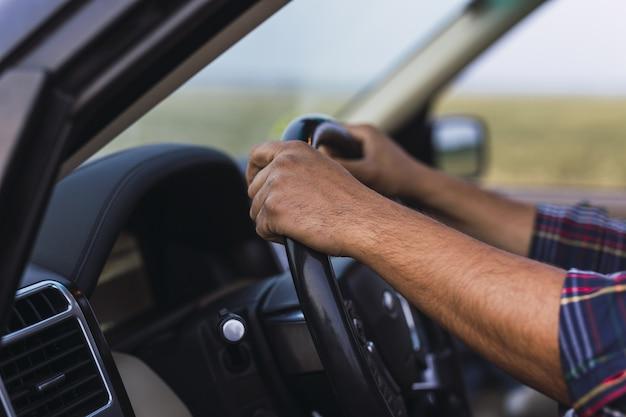 Foto aproximada das mãos de uma pessoa no volante de um carro moderno Foto gratuita