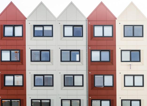 Foto aproximada de um edifício com seções vermelhas e brancas e telhados triangulares Foto gratuita