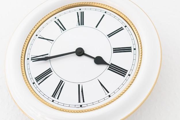 Foto aproximada de um relógio de parede branco com numeração romana Foto gratuita