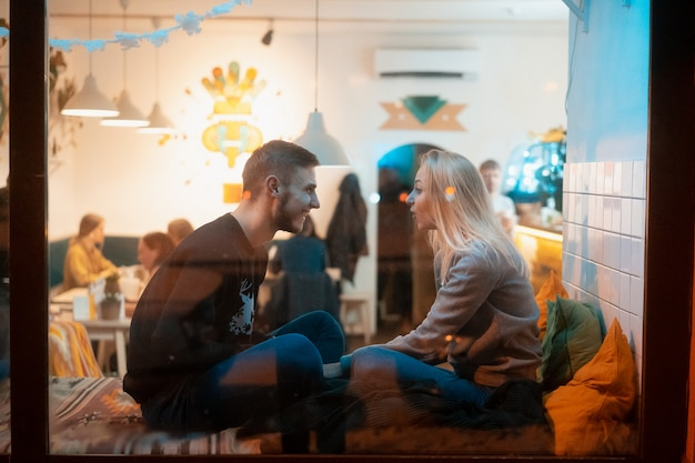 Foto através da janela. jovem casal no café com interior elegante Foto gratuita