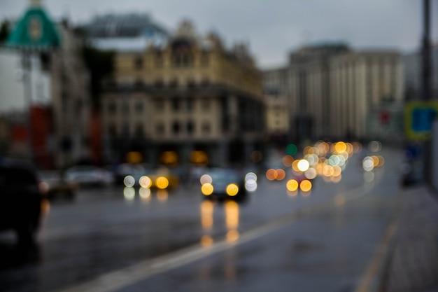 Foto borrada do fundo crepuscular da arquitetura da cidade, imagem do bokeh da rua do borrão com luzes coloridas na noite para o uso do fundo. Foto Premium