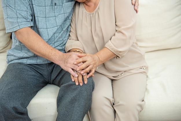 Foto colhida das mãos do casal asiático sênior mais velho bonito de mãos dadas com amor no sofá. as pessoas idosas abraçam e de mãos dadas. conceito de casal. conceito amoroso. conceito de carinho. Foto Premium