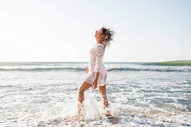 Foto completa de mulher posando na praia Foto gratuita