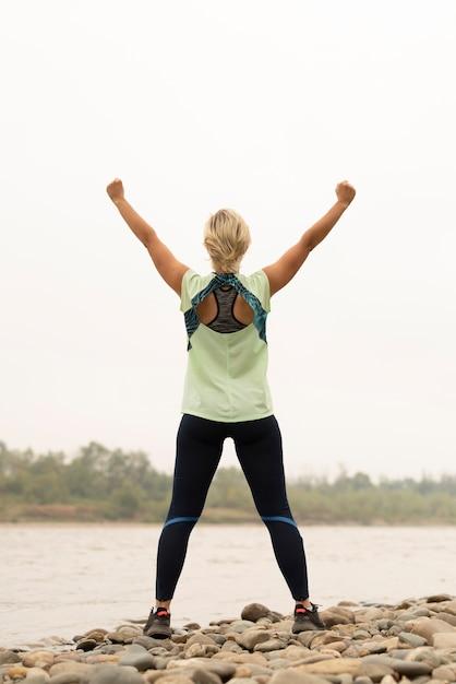 Foto completa de uma jovem mulher com os braços no ar Foto gratuita