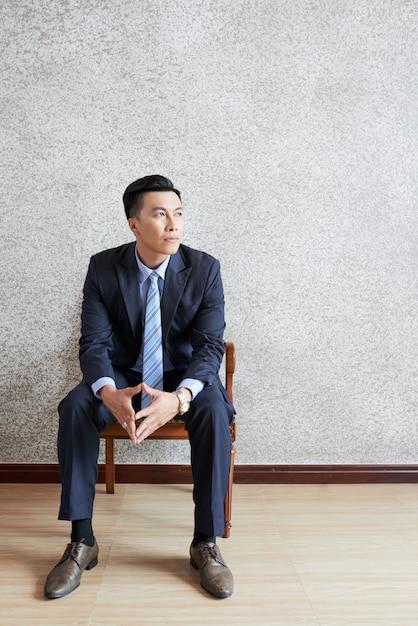 Foto completa do empresário adulto pensativo, sentado na cadeira Foto gratuita