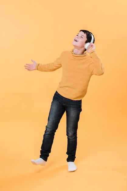 Foto completa do garoto ouvindo música com fones de ouvido Foto gratuita