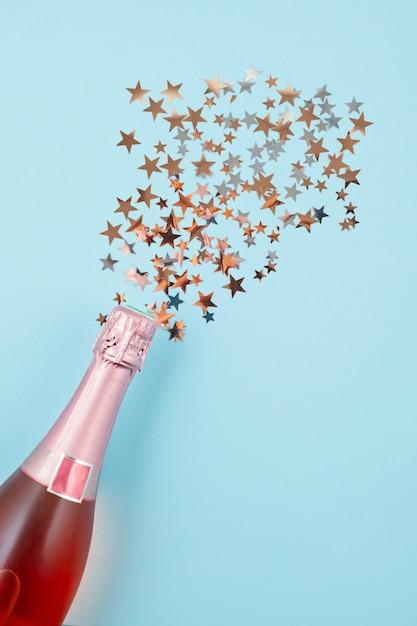Foto criativa de garrafa de champanhe com confete Foto Premium